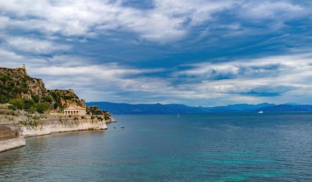 Incredibile isola rocciosa con acqua cristallina e antica architettura greca sull'isola di corfù, grecia. bellissimo paesaggio del mar ionio.