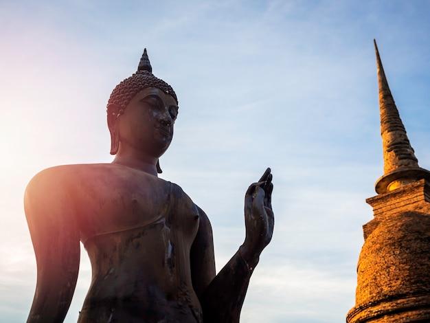 Incredibile scena della silhouette della statua del buddha e della vecchia antica pagoda al tempio wat sra sri e tra pang tra kuan nel distretto del parco storico di sukhothai, patrimonio mondiale dell'unesco in thailandia.