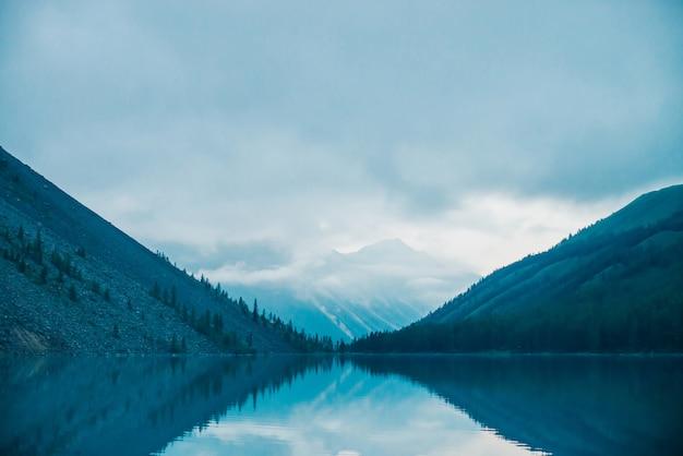 Siluette stupefacenti delle montagne e delle nuvole basse riflesse sul lago della montagna. belle increspature sullo specchio d'acqua. cielo nuvoloso in altopiani. atmosferico paesaggio spettrale. meraviglioso paesaggio montano mistico.