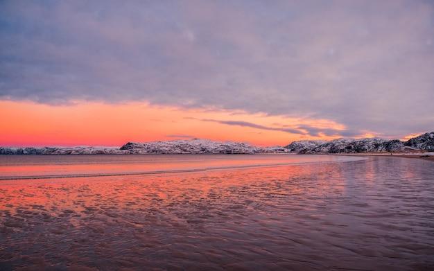 Incredibile paesaggio di alba con catena montuosa all'orizzonte vista panoramica sull'oceano artico