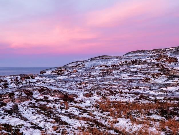 Incredibile paesaggio di alba con catena montuosa innevata bianca polare.