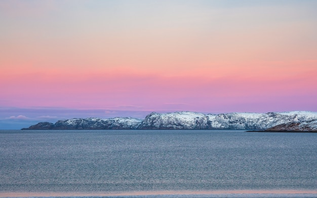 Incredibile paesaggio polare alba con catena montuosa innevata bianca all'orizzonte. vista panoramica sull'oceano artico.