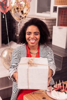 Sorprendente sorpresa. bella donna allegra che prende il suo regalo di compleanno pur essendo di ottimo umore