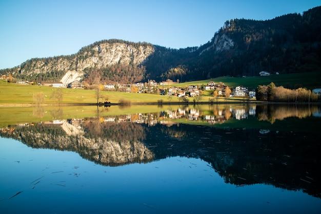Incredibile paesaggio tranquillo con area di campagna, case e colline vicino al lago e riflesso nell'acqua blu pulita su uno sfondo di cielo blu chiaro, austria.
