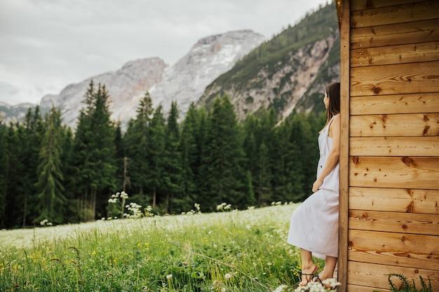 Incredibile esperienza di viaggio di bella donna tenera in abito bianco in posa laterale e guardando una vista mozzafiato sulle montagne, viaggio nelle dolomiti italiane.