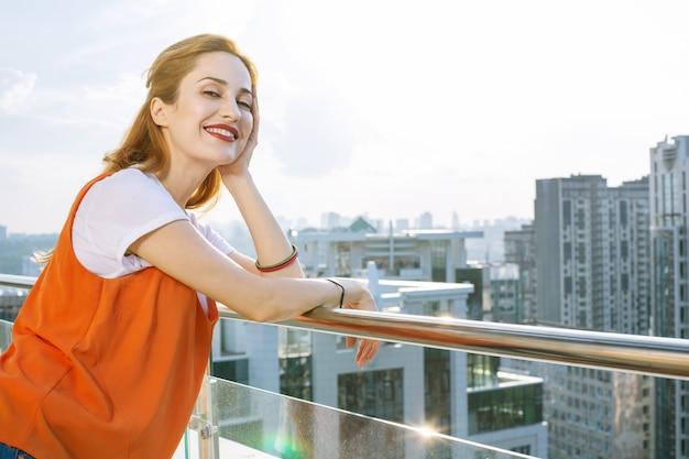 Vista spettacolare. gioiosa donna positiva in piedi sul balcone mentre vi godete la splendida vista