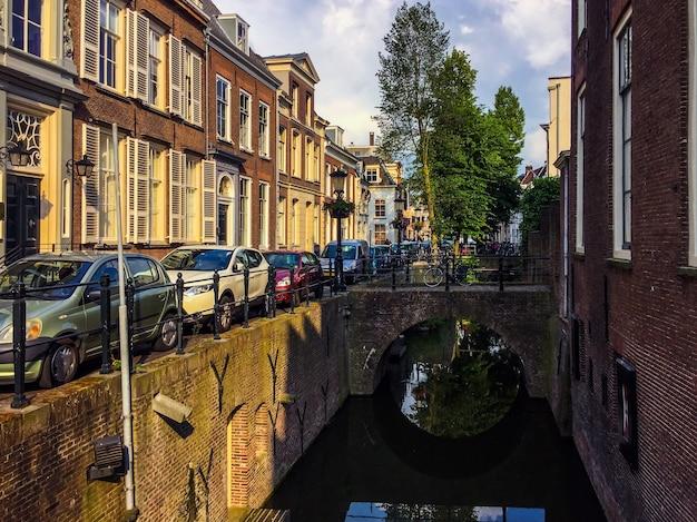 Un'incredibile vista del vecchio canale con ponti e una strada accogliente con belle case automobili e
