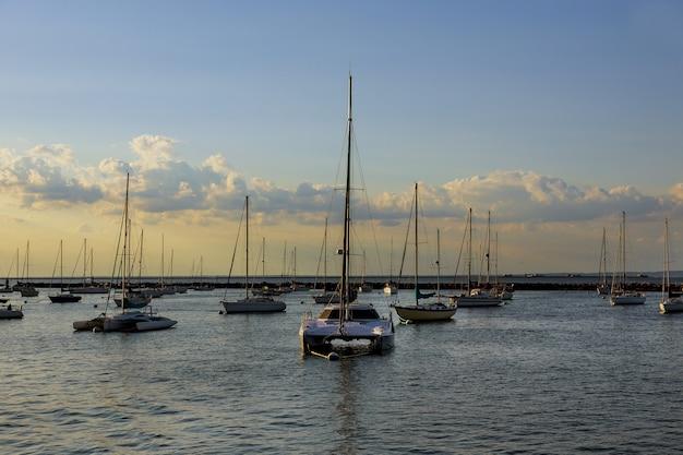 Splendida vista sulla baia privata dell'oceano con yacht al tramonto