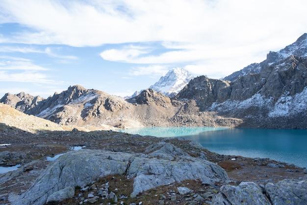 Splendida vista sulle montagne di pietra con neve e un lago di montagna