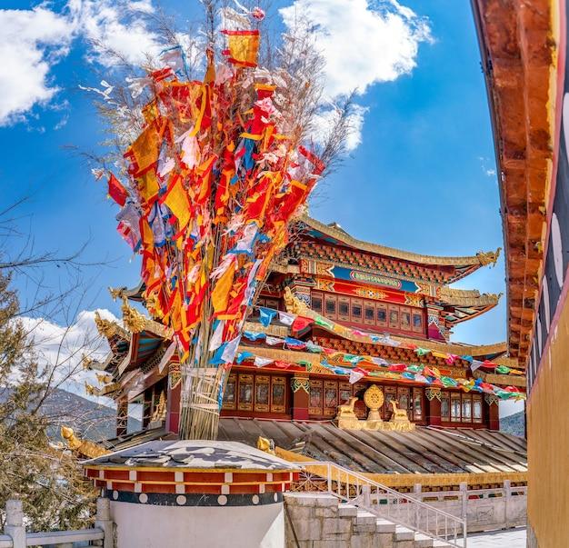 La splendida vista delle tradizionali bandiere buddiste e del tempio all'interno del monastero di guihua a shangrila in cina
