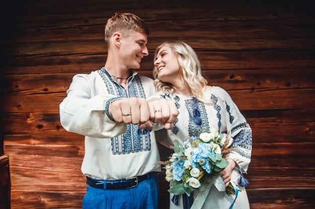 Incredibile coppia di sposi in una camicia ricamata con un mazzo di fiori