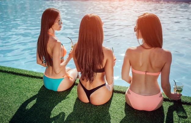 Modelli sorprendenti e ben costruiti siedono al bordo della piscina. tengono le gambe in acqua. le giovani donne si guardano e parlano. le modelle si rilassano e riposano.