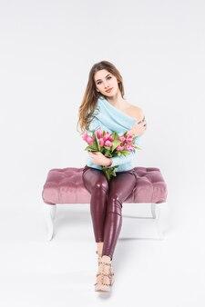 Incredibile giovane ragazza dai capelli biondi con i capelli lunghi si siede su una sedia con un mazzo di tulipani rosa nelle sue mani
