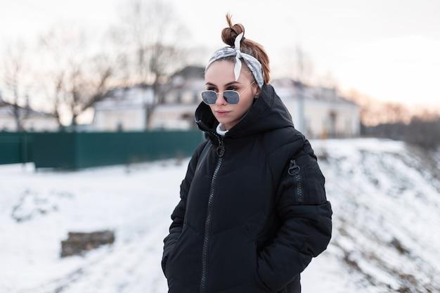 Incredibile giovane donna alla moda hipster con un'acconciatura alla moda con un'elegante bandana in occhiali da sole alla moda in un cappotto nero invernale