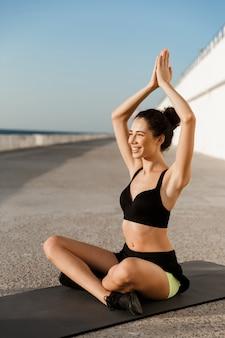 Incredibile giovane donna sportiva fa esercizi di yoga meditare all'aperto sulla spiaggia.