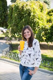 Incredibile giovane donna con un sorriso carino in posa con il vetro sullo sfondo della natura