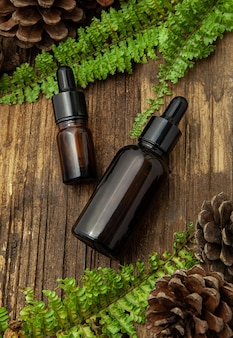 Flaconi per la cosmetica in vetro ambrato con foglie verdi su fondo in legno. concetto naturale. vista piana, vista dall'alto.