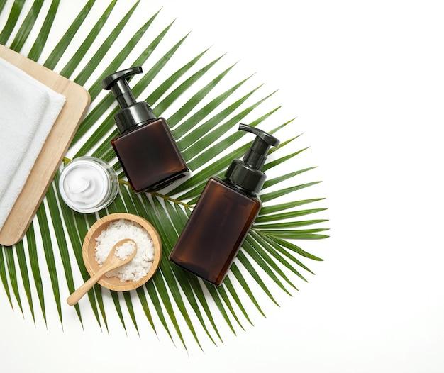 Flaconi per la cosmetica in vetro ambrato con elemento spa e asciugamano con foglia verde su fondo in marmo. vista piana, vista dall'alto.