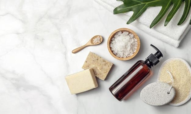Flaconi per la cosmetica in vetro ambrato con elemento spa e asciugamano con foglia su sfondo di marmo. vista piana, vista dall'alto.