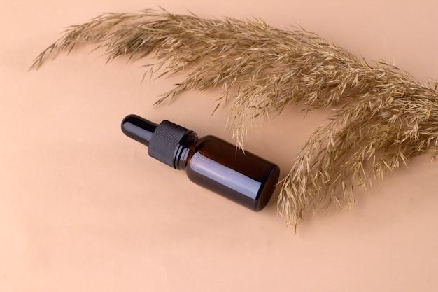 Bottiglia di olio essenziale di vetro ambrato con pipetta su fondo beige