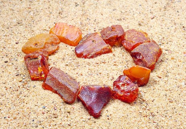 Ambra a forma di cuore nella sabbia