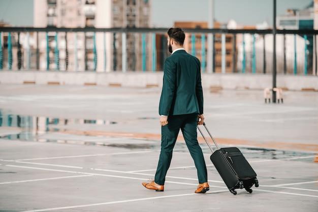 Ambizioso uomo d'affari barbuto caucasico in abbigliamento formale che trasportano bagagli e camminando sul parcheggio. concetto di viaggio d'affari. schiena girata. il successo si verifica quando i tuoi sogni diventano più grandi delle tue scuse.