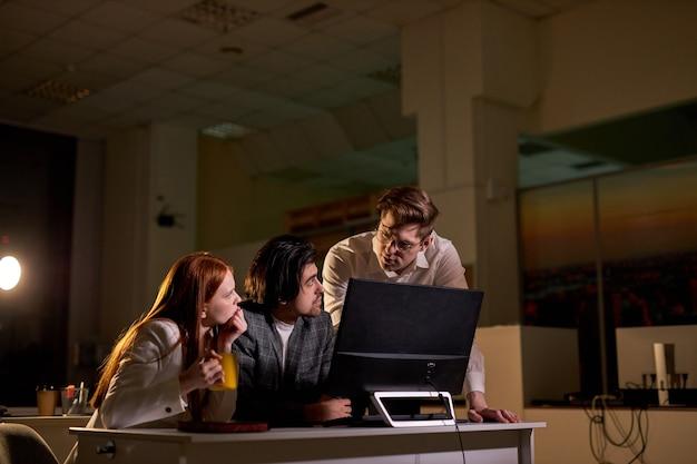 Gente di affari ambiziosa e fiduciosa che utilizza computer desktop, di notte, discutendo spiegando compiti specifici, gestione degli account e mosse strategiche. persone a tarda notte nel grande ufficio aziendale