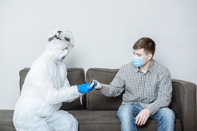 Un medico dell'ambulanza in una tuta protettiva individuale ppe esamina il paziente e misura il livello di ossigeno utilizzando un pulsossimetro
