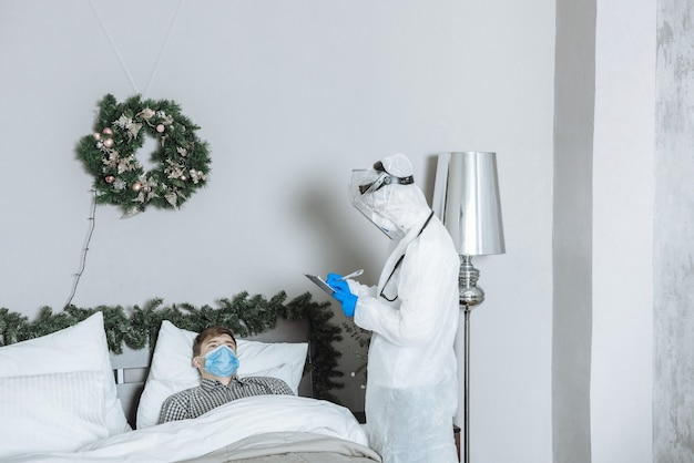 Un medico dell'ambulanza in una tuta protettiva ppe hazmat esamina un paziente malato con coronavirus covid-19 prima di capodanno e natale