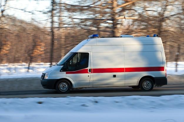 Ambulanza che va su una strada invernale con sfondo blured