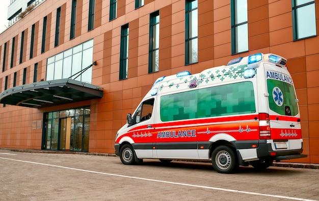 Un'ambulanza si trova davanti a un moderno ospedale. chiamata a domicilio medico, concetto di assistenza sanitaria.