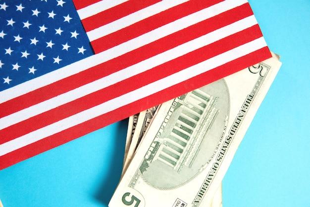 Bandiera e dollari dell'america sulla superficie blu