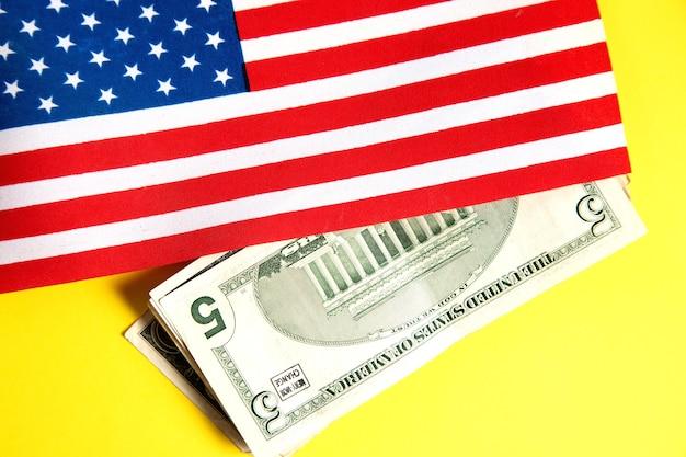 Bandiera americana e dollari sulla superficie gialla