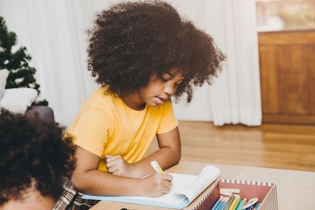 Bambini neri americani in età prescolare che fanno i compiti imparando l'istruzione con sua sorella che vive insieme a casa.