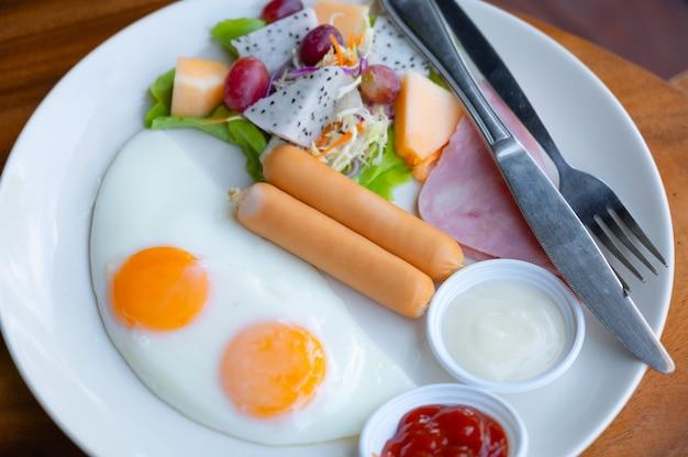 Colazione americana con salsicce, uova fritte e insalata di frutta e verdura.