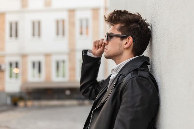Il giovane brutale americano con un'acconciatura alla moda in una giacca di pelle nera oversize alla moda raddrizza occhiali da sole scuri vintage vicino a un muro grigio all'aperto. ragazzo urbano in posa in città per strada