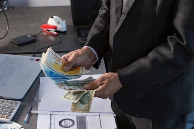 Mani dell'uomo d'affari americano che tengono un fan di soldi di nuovi shekel israeliani e valuta di dollari. l'immagine ritagliata della mano contiene banconote da 100 e 200 shekel. messa a fuoco selettiva. il banchiere conta i soldi in ufficio