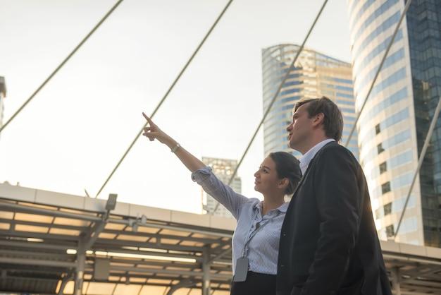 La donna d'affari americana punta il dito verso l'edificio moderno con il suo capo per discutere della costruzione di un progetto di investimento immobiliare con la luce del tramonto nella città moderna urbana.