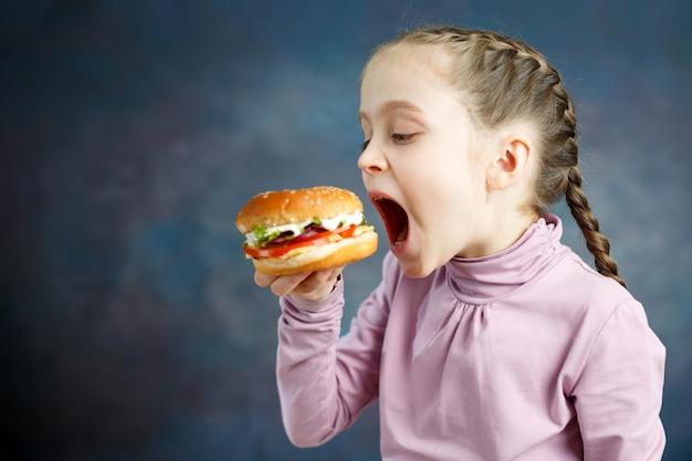 Pasto grasso calorico americano cibo spazzatura, la bambina si diverte a mangiare hamburger fast food hamburger malsano