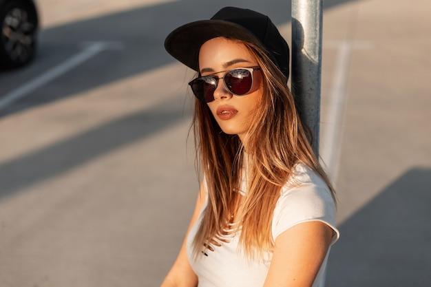 Ragazza alla moda americana in berretto nero alla moda in occhiali da sole vintage in abiti estivi che riposano sulla strada al tramonto. ritratto bella ragazza sexy sul parcheggio all'aperto in giornata di sole.