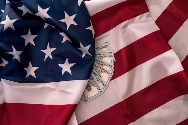 Banconote del dollaro americano sul primo piano della bandiera nazionale