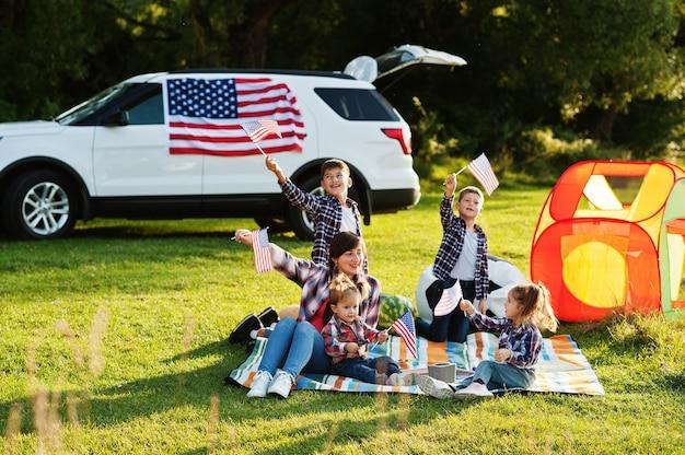 Famiglia americana che trascorre del tempo insieme. con le bandiere degli stati uniti contro la grande auto suv all'aperto.