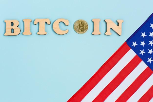 Bandiera americana, bitcoin e lettere di legno sulla superficie blu