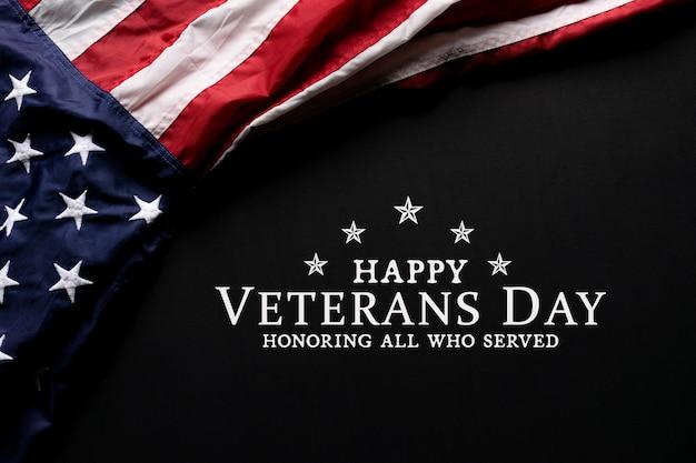 Bandiera americana su sfondo nero con testo happy veterans day.