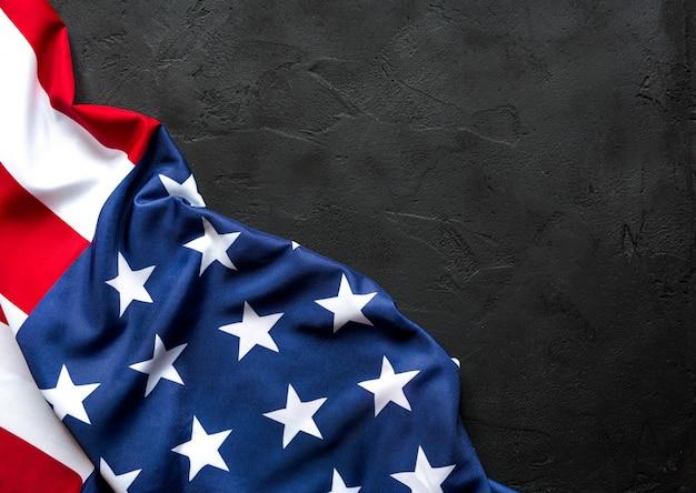 Bandiera americana sul tavolo di cemento scuro nero con spazio di copia.