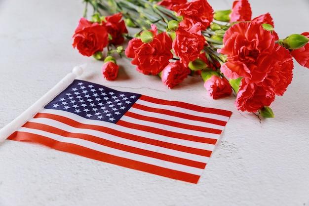 Bandiera americana e fiori su superficie bianca