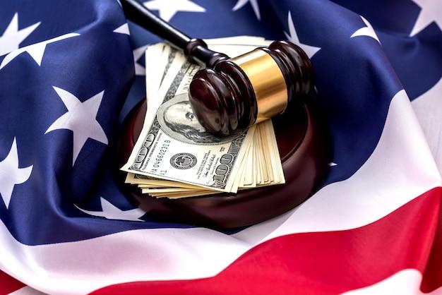 Banconote in dollari, martelletto e bandiera americana