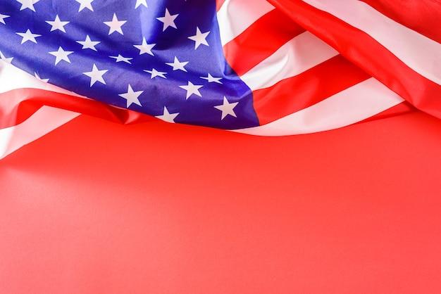 Bandiera americana piegata in modo informale nella parte superiore su uno sfondo rosso isolato con spazio per le copie.