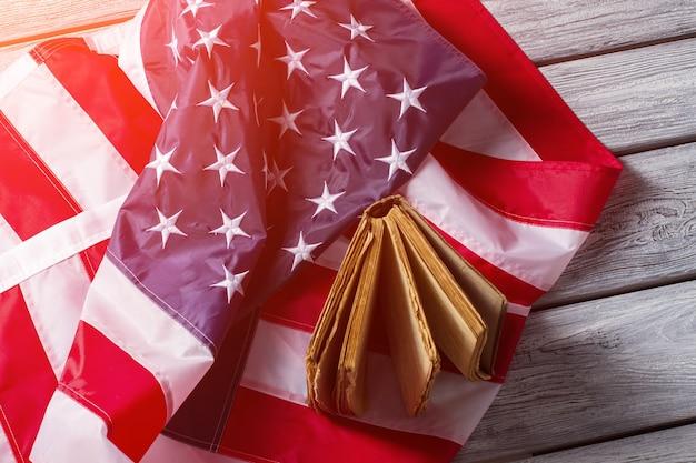 Bandiera americana e vecchio libro. bandiera e libro sotto la luce del sole. diritti e libertà della nazione. storia, cultura e tradizioni.