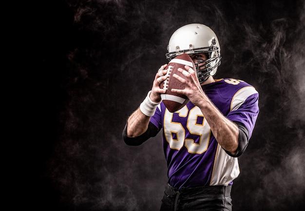 Palla della tenuta del giocatore di football americano in sue mani in fumo. muro nero, copia spazio. il concetto di football americano, motivazione, spazio di copia